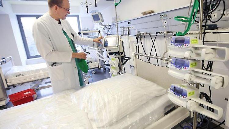 Ein Arzt steht neben einem Intensivbett im Krankenhaus. Foto: Roland Weihrauch/dpa/Symbolbild