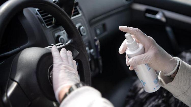 Ein Taxi-Fahrer desinfiziert den Innenraum seines Taxis. Foto: Sina Schuldt/dpa