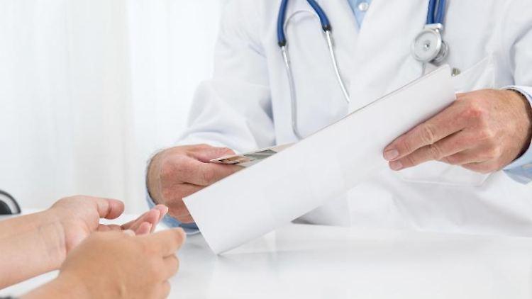 Ein Arzt hält ein Blatt Papier in der Hand. Foto: Christin Klose/dpa-tmn