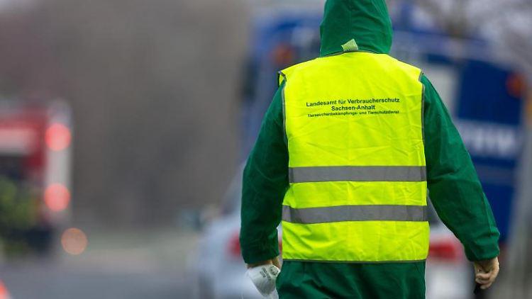 Eine Frau in Schutzbekleidung und einer Warnwest geht zu geparkten Einsatzfahrzeugen. Foto: Klaus-Dietmar Gabbert/dpa-Zentralbild/dpa