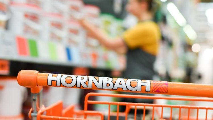Eine Mitarbeiterin steht in in einem Baumarkt hinter einem Einkaufswagen. Foto: Uwe Anspach/dpa/Archivbild