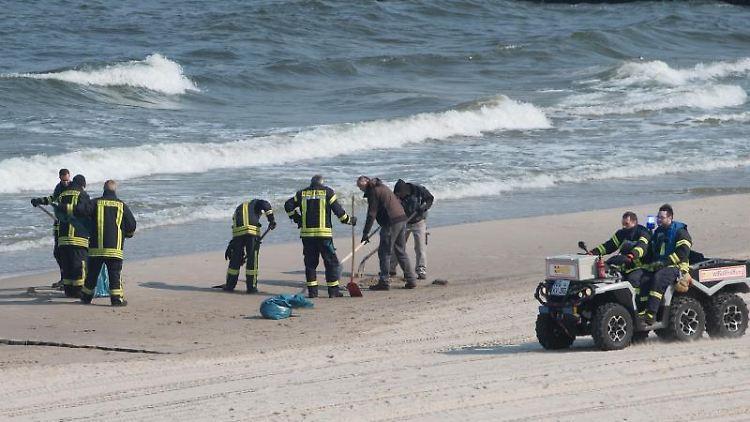 Feuerwehrleute sammeln am Strand der Insel Usedom schwarze, fetthaltige Klumpen mit Schaufeln ein. Foto: Stefan Sauer/dpa-Zentralbild/dpa