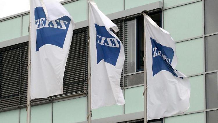 Fahnen wehen vor dem Gebäude der Carl Zeiss Meditec AG in Jena. Foto: Bodo Schackow/zb/dpa