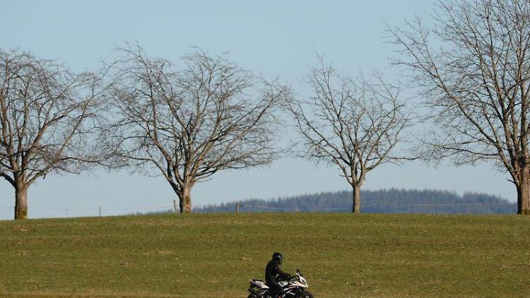Ein Motorradfahrer fährt über eine Straße. Foto: picture alliance / dpa/Symbolbild