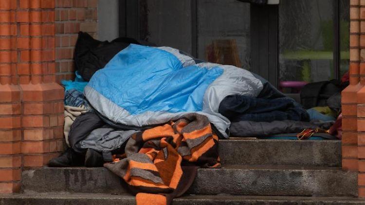 Ein Obdachloser liegt unter einer Decke in einem Eingang einer Kirche in Kreuzberg. Foto: Paul Zinken/dpa/Archivbild