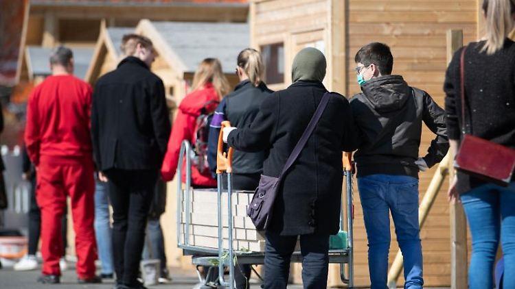 Kunden stehen Schlange vor einem Baumarkt in Osnabrück. Foto: Friso Gentsch/dpa