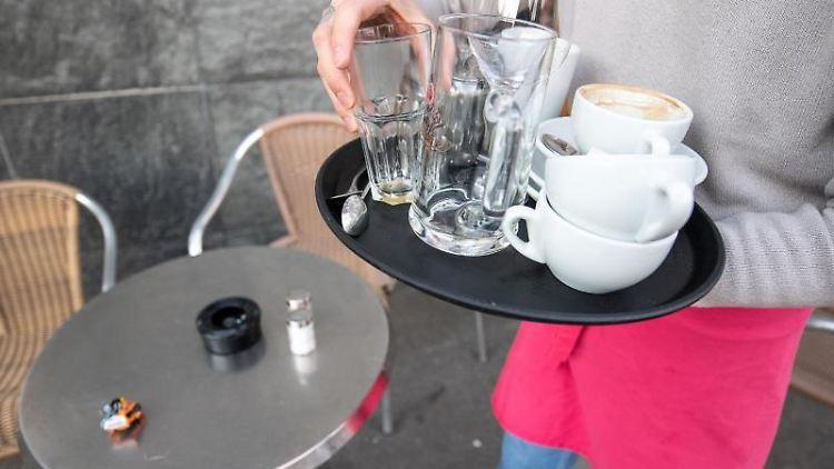 Ein Kellner räumt einen Tisch in einem Restaurant ab. Foto: Sebastian Gollnow/dpa/Archivbild/Symbolbild