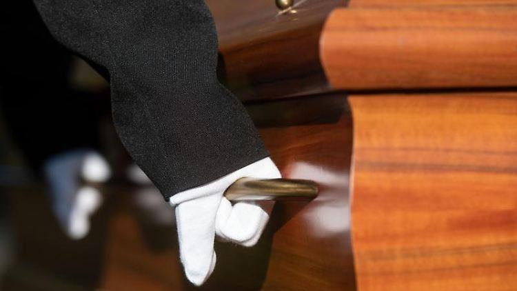 Sargträger mit weißen Handschuhen tragen einen Sarg. Foto: Bernd Thissen/dpa/Archivbild/Illustration