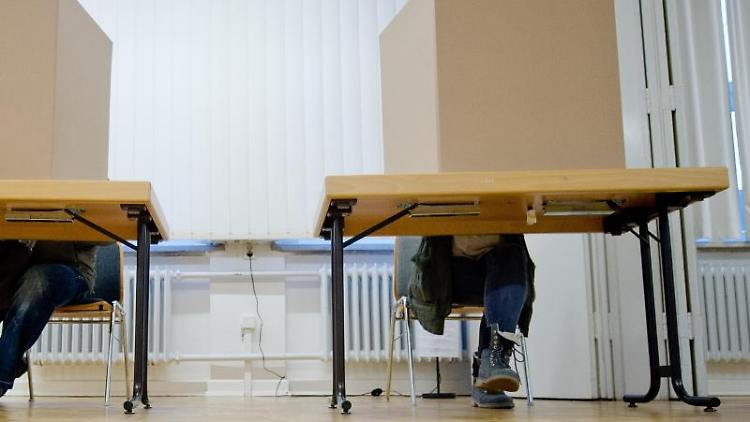 Ein Mann und eine Frau füllen in einer Wahlkabine ihren Stimmzettel aus. Foto: picture alliance/dpa/Symbolbild
