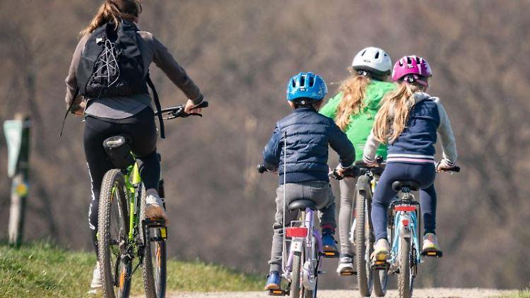 Eine Frau ist mit drei Kindern auf dem Fahrrad unterwegs auf einem Feldweg im Stadtteil Bergen. Foto: Frank Rumpenhorst/dpa/Archivbild