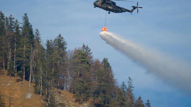 Ein Hubschrauber mit einemWassertank überfliegt den Schwarzberg. Foto: Sven Hoppe/dpa/Archivbild