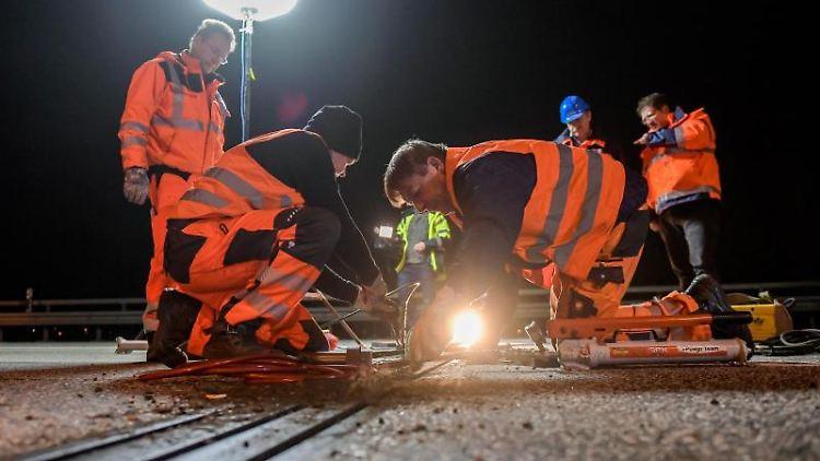 Techniker untersuchen auf der Autobahn A7 kurz vor dem Elbtunnel den Zustand einer Brückenlamelle. Foto: Axel Heimken/dpa/Archivbild