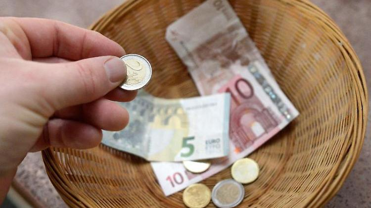 Eine Hand gibt Geld in einen Sammelkorb. Foto: Henning Kaiser/dpa/Symbolbild