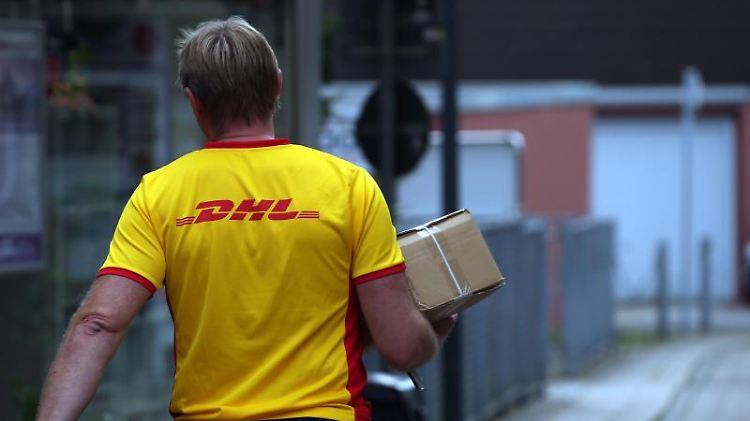 Ein Paketzusteller der von Deutsche Post DHL liefert ein Paket aus. Foto: picture alliance / dpa/Archivbild