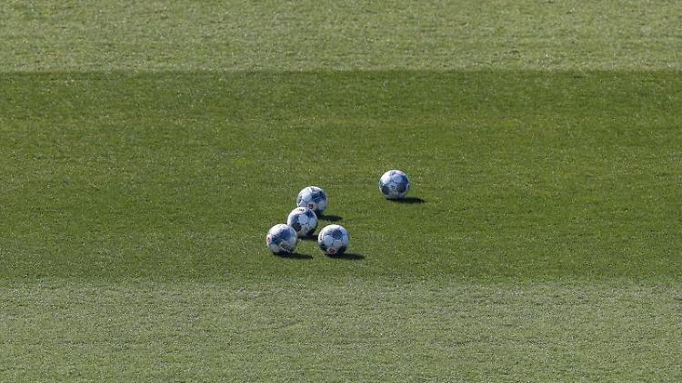Fünf Bälle liegen auf dem Rasen. Foto: Guido Kirchner/dpa/Archivbild