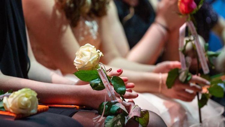 Jugendliche halten Rosen in den Händen. Foto: Monika Skolimowska/dpa-Zentralbild/dpa/Archivbild