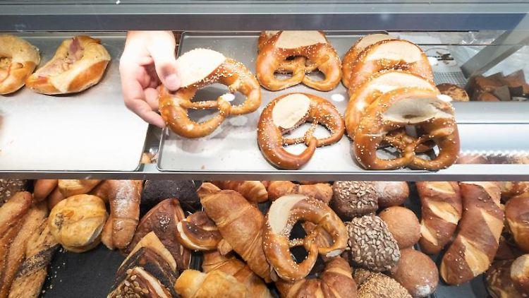 Ein Hand nimmt in einer Bäckerei eine Brezel aus einer Auslage. Foto: Bernd Weissbrod/dpa/Symbolbild