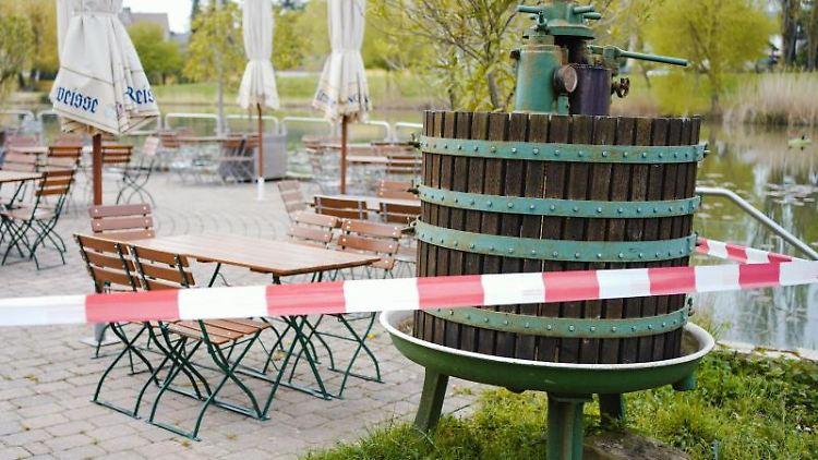 Ein Absperrband hängt um eine Terrasse mit leeren Tischreihen und einer Weinpresse. Foto: Uwe Anspach/dpa