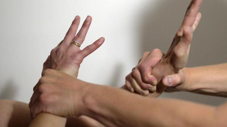 Die Arme eines Mannes (r) halten mit Gewalt die Arme einer Frau fest. Foto: Maurizio Gambarini/dpa/Symbolbild