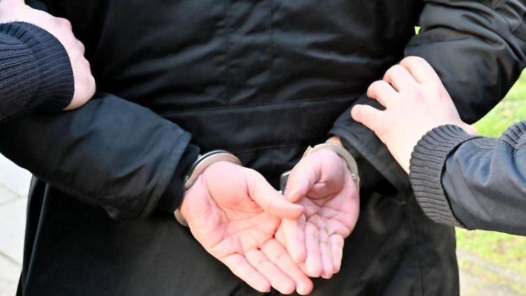 Ein Mann wird in Handschellen abgeführt. Foto: Carsten Rehder/dpa/Symbolbild