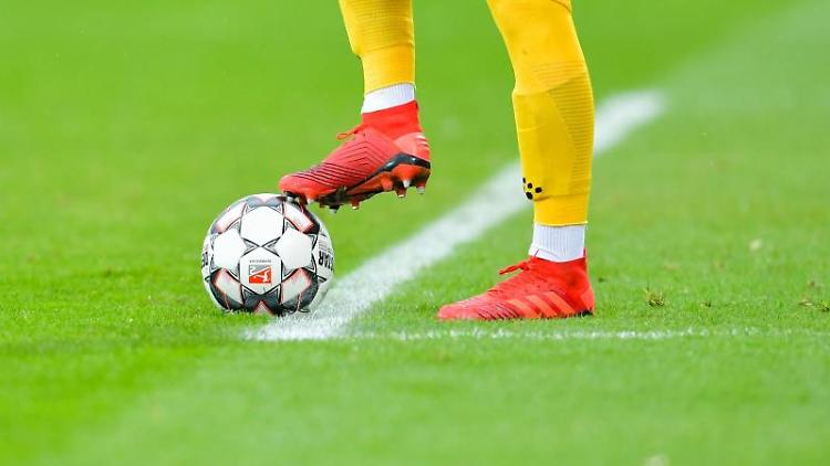 Ein Fußball wird über das Spielfeld geschossen. Foto: Uwe Anspach/dpa/Symbolbild