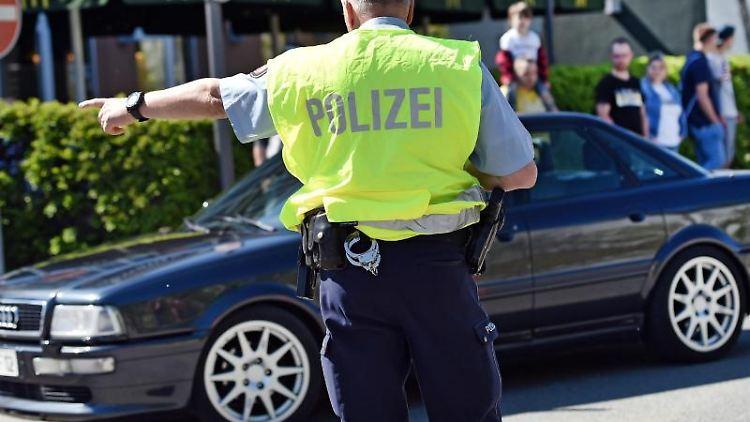 Ein Polizist winkt ein getuntes Auto raus. Foto: Caroline Seidel/dpa/Symbolbild