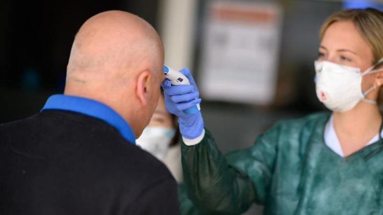 Eine Ärztin misst die Temperatur eines Mannes. Foto: Sebastian Gollnow/dpa