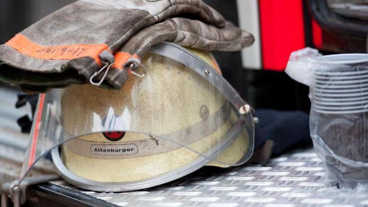 Ein Feuerwehrhelm liegt an einem Einsatzfahrzeug. Foto: picture alliance/dpa/Symbolbild
