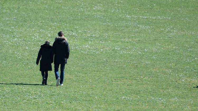 Zwei Menschen gehen über eine Wiese. Foto: Sebastian Gollnow/dpa/Archivbild