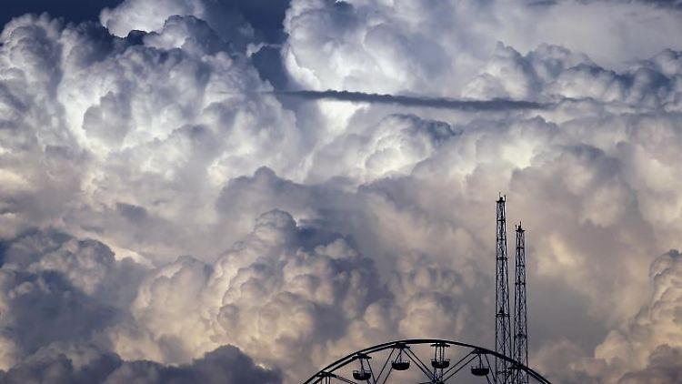 Wolken türmen sich über den Fahrgeschäften des Freizeitparks