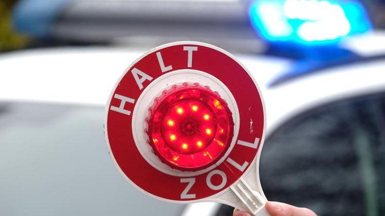 Eine Haltekelle des Zolls wird vor das Blaulicht eines Einsatzfahrzeuges gehalten. Foto: Sebastian Willnow/dpa-Zentralbild/dpa/Symbolbild