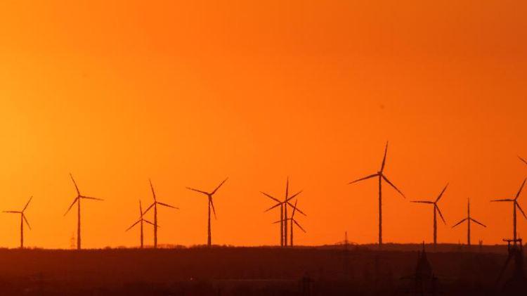 Die aufgehende Sonne hinter Windrädern bei Hannover. Foto: Julian Stratenschulte/dpa