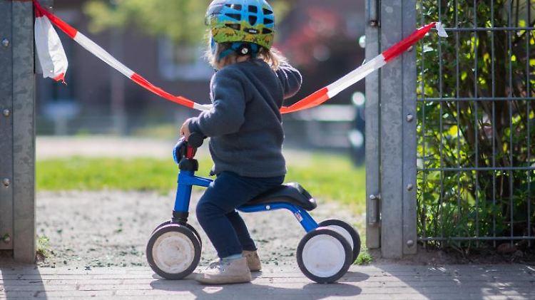 Ein kleines Mädchen steht vor einem abgesperrten Spielplatz. Foto: Julian Stratenschulte/dpa/Archivbild