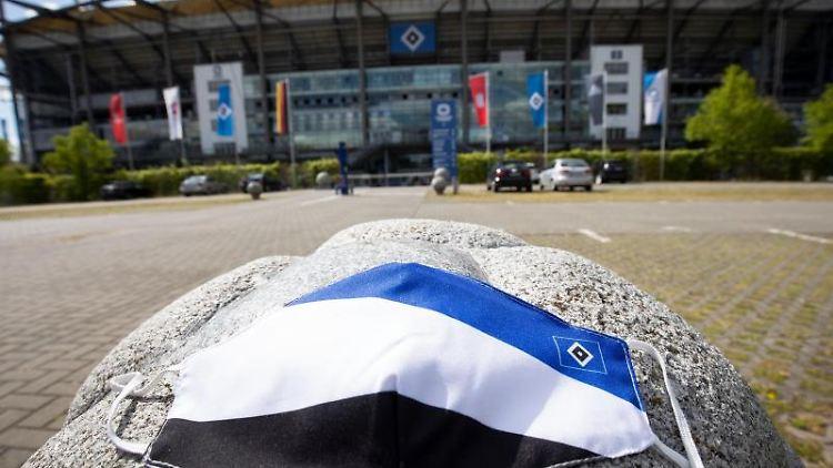 Ein Mundschutz in den Farben des HSV liegt vor dem Volkspark Stadion. Foto: Christian Charisius/dpa