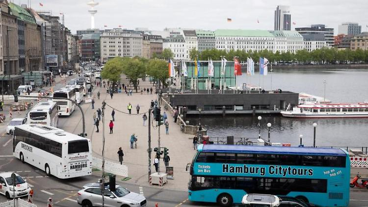 Zahlreiche Reisebusse nehmen an einem Buskorso um die Binnenalster teil. Foto: Christian Charisius/dpa