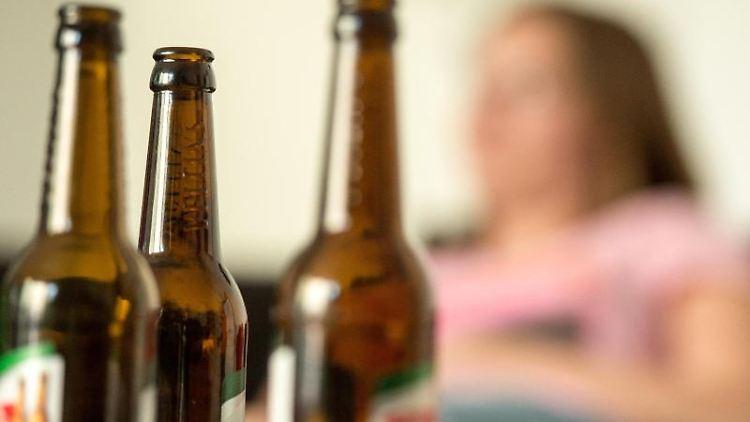 Eine junge Frau sitzt hinter leeren Bierflaschen. Foto: Alexander Heinl/dpa