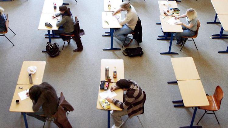 Schülerinnen und Schüler absolvieren eine Prüfung. Foto: Roland Weihrauch/dpa/Archivbild