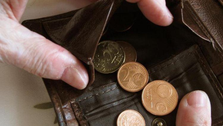 Eine Frau hält eine nahezu leere Geldbörse in den Händen. Foto: Jens Kalaene/dpa-Zentralbild/dpa/Illustration