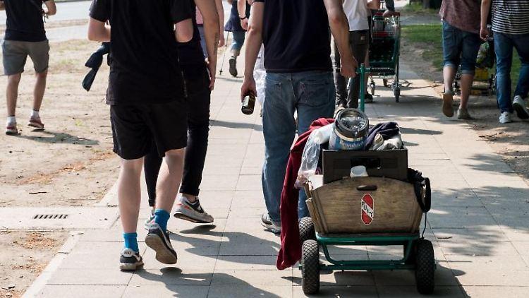 Junge Leute ziehen am Vatertag einen Bollerwagen und Einkaufswagen während einer Vatertags-Tour. Foto: Peter Steffen/dpa/Archivbild