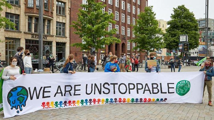 """Teilnehmer der Fridays for Future-Demo auf dem Gänsemarkt halten ein Transparent mit der Aufschrift: """""""