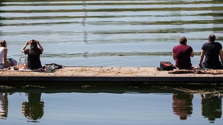 Mit Abstand zueinander genießen zwei Frauen und zwei Männer am Vatertag das sonnige Wetter am Max-Eyth-See. Foto: Christoph Schmidt/dpa/Archivbild