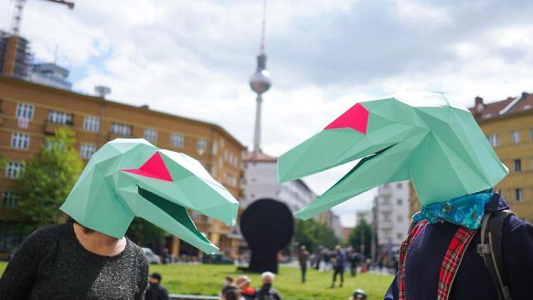 Zwei als Echsen verkleidete Demonstranten vor der Berliner Volksbühne. Foto: Jörg Carstensen/dpa/Archivbild