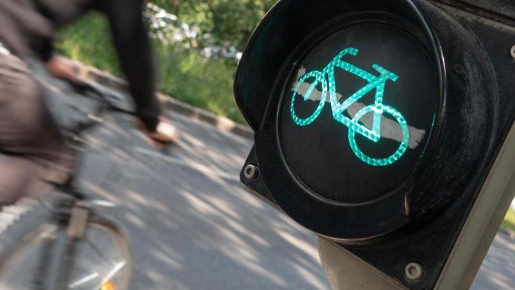 Ein Radfahrer fährt auf der Theodor-Heuss-Straß an einer grünen Fahrradampel vorbei. Foto: Gregor Bauernfeind/dpa