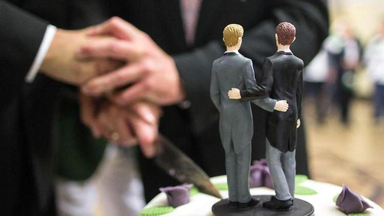 Zwei Männer schneiden nach ihrer Eheschließung eine Hochzeitstorte an. Foto: Ina Fassbender/dpa/Symbolbild