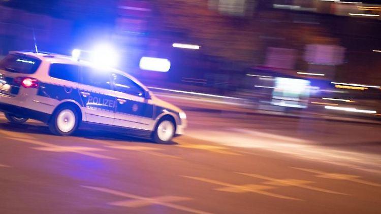 Ein Polizeiauto fährt unter Einsatz von Blaulicht und Sirene eine Straße entlang. Foto: Lino Mirgeler/dpa/Symbolbild