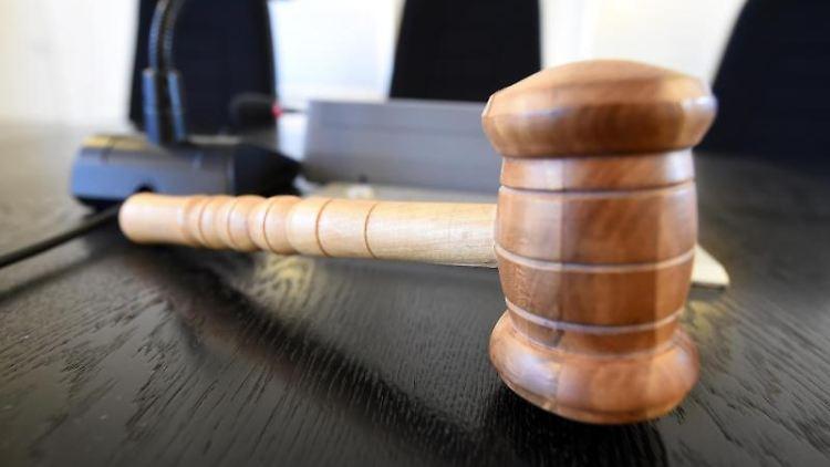 Auf einer Richterbank liegt ein Richterhammer aus Holz. Foto: Uli Deck/dpa/Symbolbild