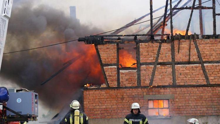 Einsatzkräfte der Feuerwehr löschen das Feuer auf dem Hof in der Gemeinde Urbach. Foto: Kohls/SDMG/dpa