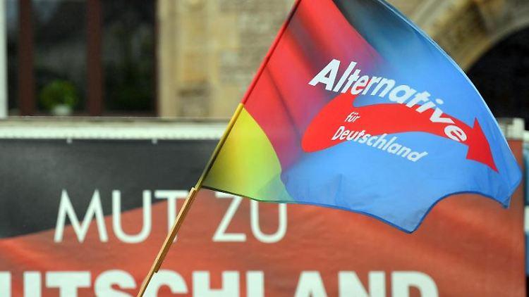 Eine Fahne mit dem Parteilogo der AfD weht während einer Kundgebung. Foto: Hendrik Schmidt/dpa-Zentralbild/ZB