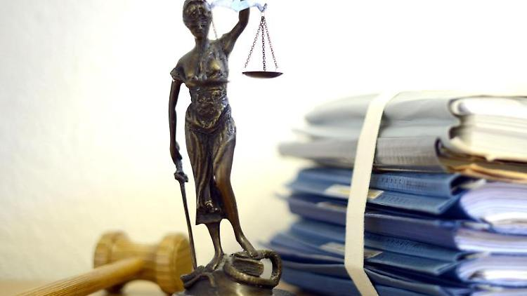 Justitia mit Holzhammer und Aktenstapel. Foto: Volker Hartmann/dpa/Symbolbild