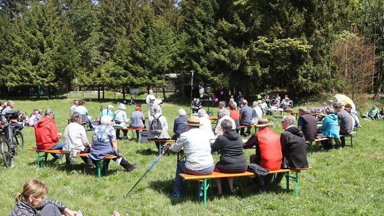 Besucher eines evangelischen Gottesdienstes sitzen auf einer Wiese auf Bänken. Foto: Bodo Schackow/dpa-Zentralbild/dpa/Archivbild